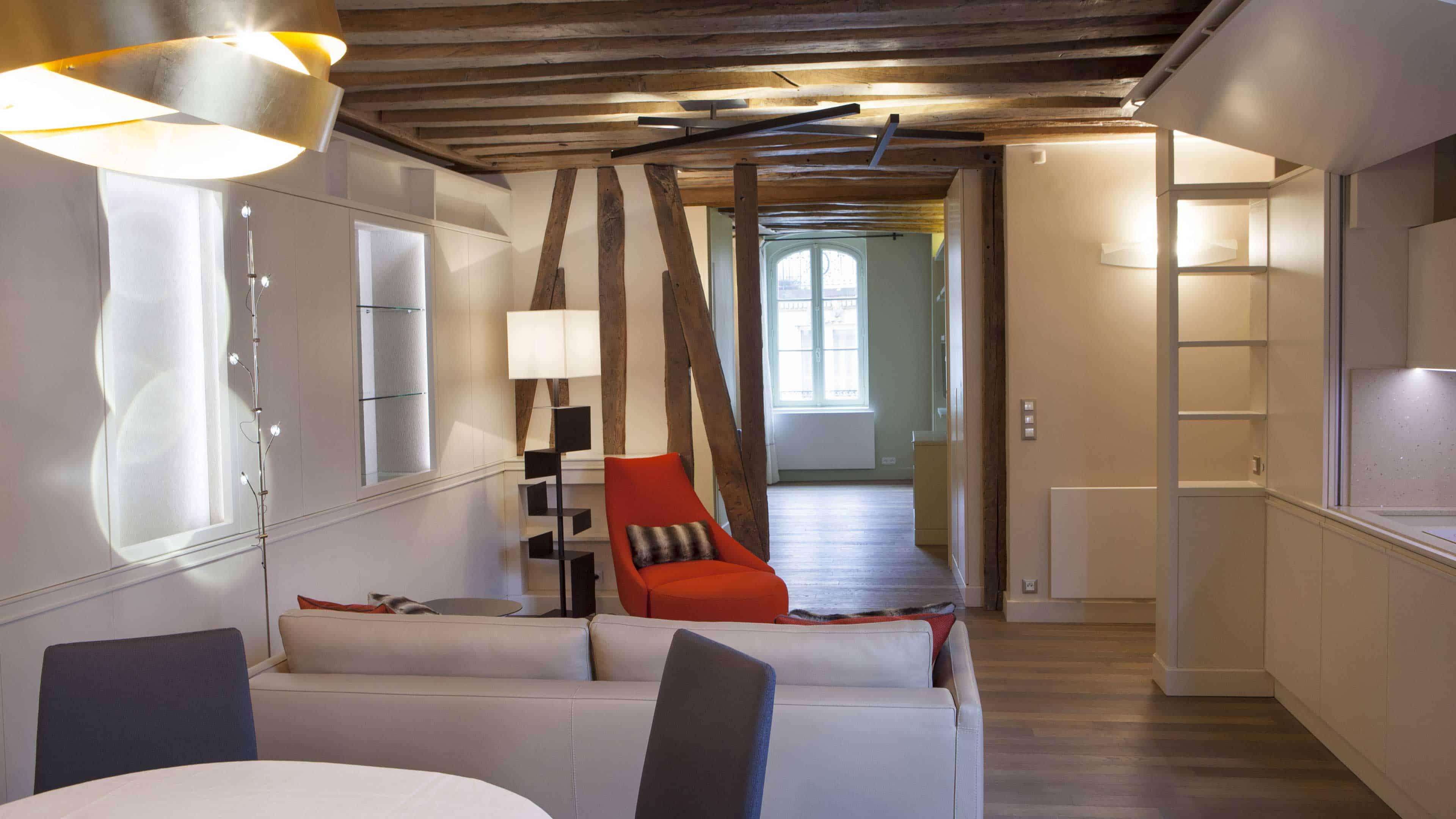 Au cœur de Saint-Germain, cet espace de caractère résulte de la réunion de deux appartements situés au cœur du 6ème. La restauration soigneuse des poutres et des colombages d'origine a permis de révéler le potentiel du lieu. Le résultat est un espace unique et ouvert, qu'il est possible de diviser grâce à de grands panneaux coulissants pour préserver l'intimité de la chambre. Parfaitement intégrée dans la boiserie moderne du salon, la cuisine sur-mesure en bois latté satiné peut également se fermer pour se fondre littéralement dans le décor.