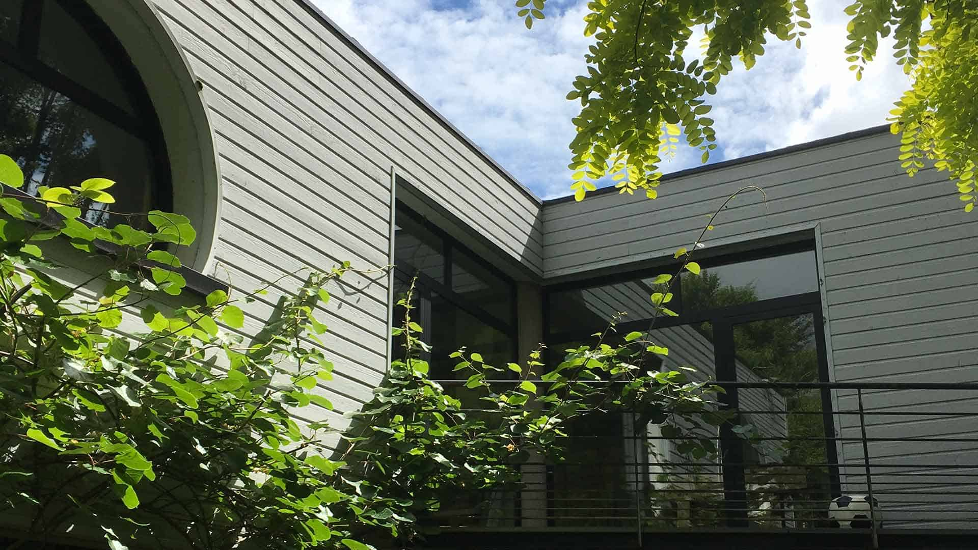Cette maison comprend une partie ancienne datant du 20ème siècle et une partie moderne de 1991. Le projet d'extension ses situe dans le prolongement de la partie moderne de la maison et s'intègre parfaitement à l'environnement existant. La pièce de vie a été agrandie de 20m2 et un abri à vélos fermés a été créé entièrement. Le toit de cette extension est aménagé en terrasse vitrée contemporaine. Elle est accessible à la fois par la chambre à coucher et par un escalier extérieur en métal réalisé sur-mesure. Le choix de larges menuiseries et baies vitrées apporte de la luminosité dans ce nouvel espace.
